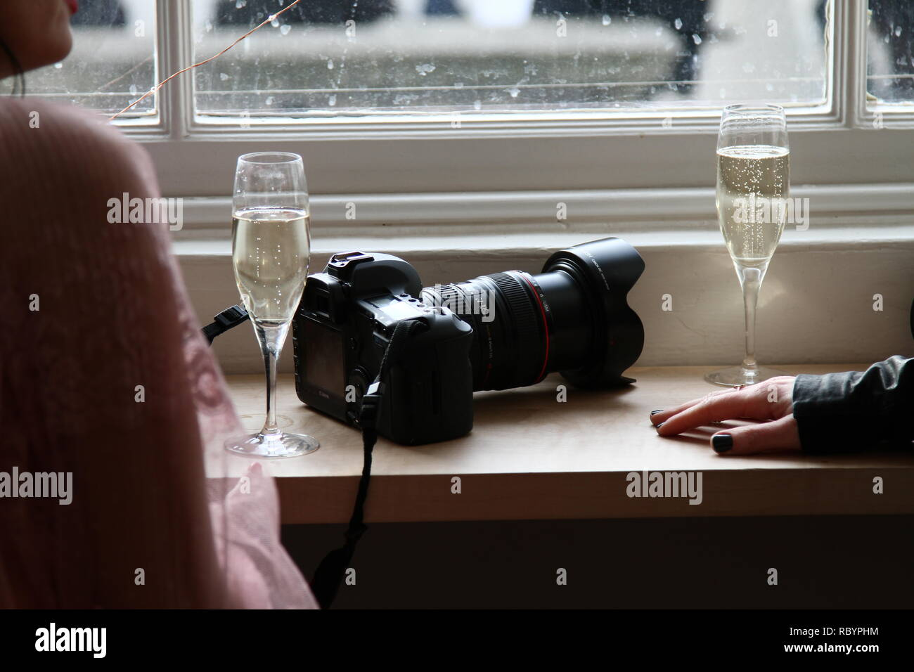 Two members of the public having a drink in a public house with water stained windows and a Canon camera and lens on window shelf [ seal ]. The people were unaware of this photograph being taken. The image could be cropped slightly and then used as the perfect book cover . Moody book cover. Stock Photo