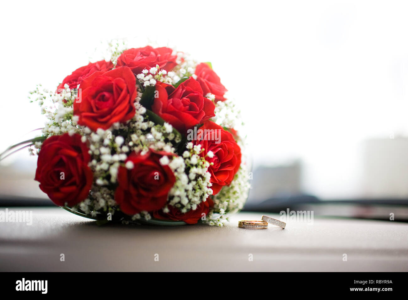 Close Up Of A Pair Of Wedding Rings Behind Them A Bouquet Of Red Flowers Stock Photo Alamy