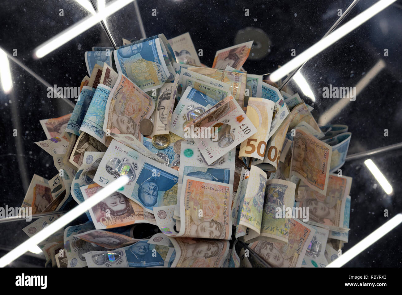 A pile of British sterling paper and polymer money £5 and £10 bank notes in a collection box  with light reflections in London UK  KATHY DEWITT - Stock Image