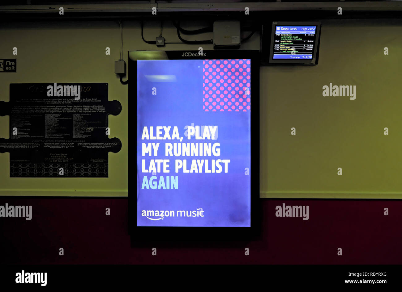 'Alexa Play My Running Late Playlist Again'  Amazon Music advert on an electronic billboard at a railway station in Great Britain UK  KATHY DEWITT - Stock Image
