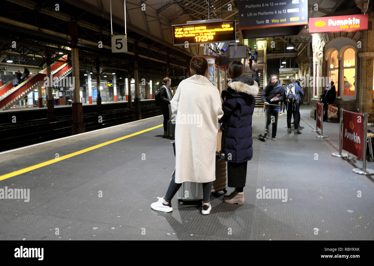 Rear view of passengers woman wearing white coat standing on platform at Crewe railway station waiting for a Virgin train to London UK    KATHY DEWITT - Stock Image