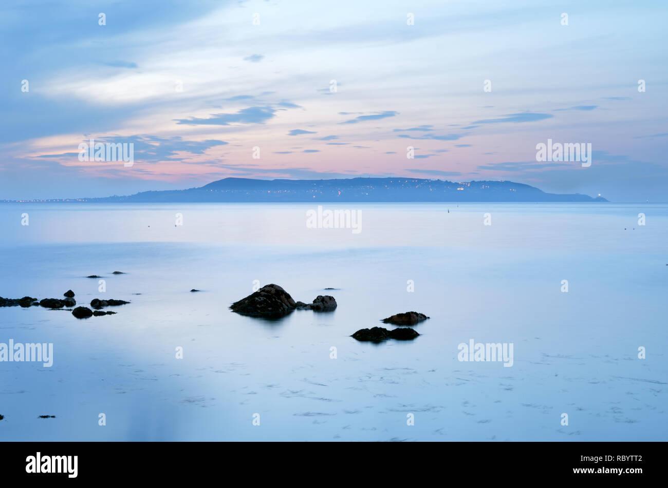 Flat calm sea,windless day,peninsula of howth,suburb of county dublin as seen across dublin bay,ireland. Stock Photo