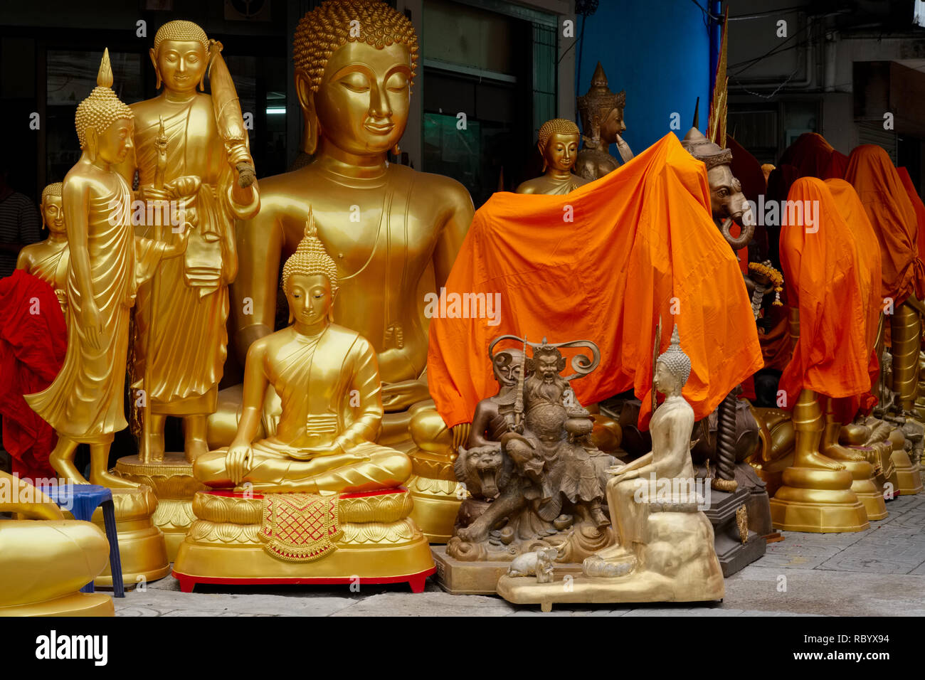 Buddha statues at a shop selling religious artifacts in Bamrung Muang Rd., Bangkok, Thailand, some covered with orange cloth for the night's 'sleep' - Stock Image