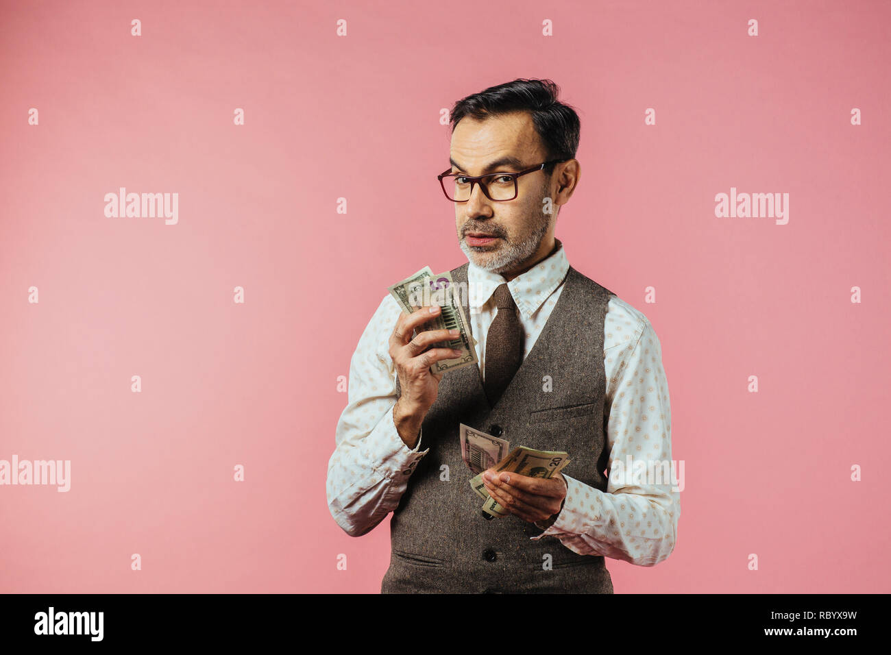 Portrait of a mature man in brown vest holding dollar bills and looking at camera, isolated on pink studio background Stock Photo