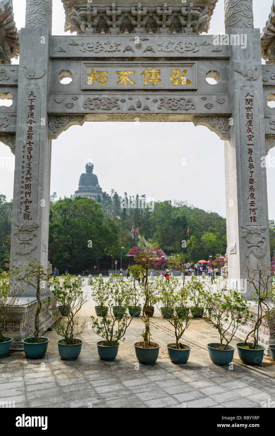 Framed view of the Tian Tan Buddha through the Mountain Gate and the Literary Couplet at the Po Lin Monastery, Lantau Island, Hong Kong - Stock Image