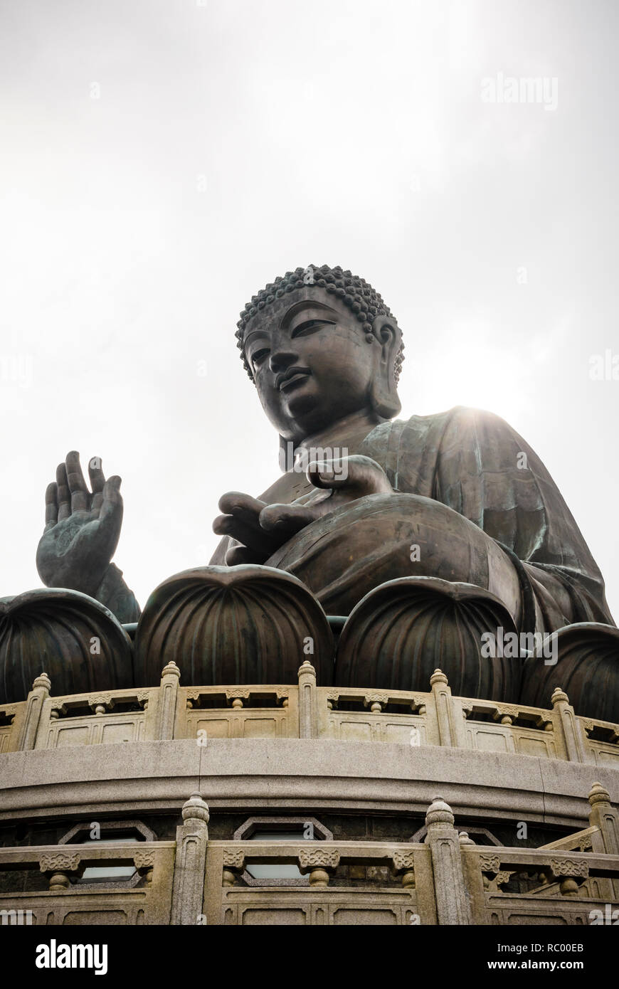Sun rays break through the cloud to reflect off the shoulder of the bronze Tian Tan Buddha, Lantau Island, Hong Kong - Stock Image