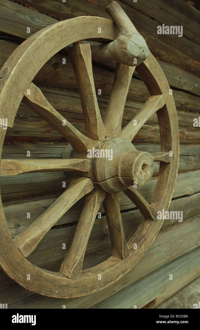 old wooden cartwheel hanging on barn wall - Stock Image