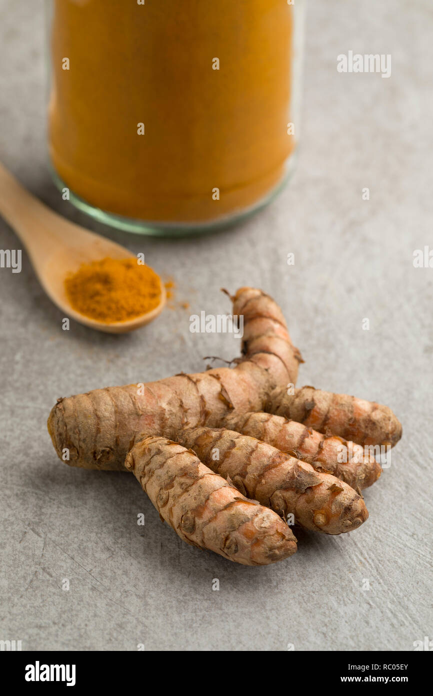 Fresh raw turmeric rhizome and powder in a jar and on a wooden spoon - Stock Image