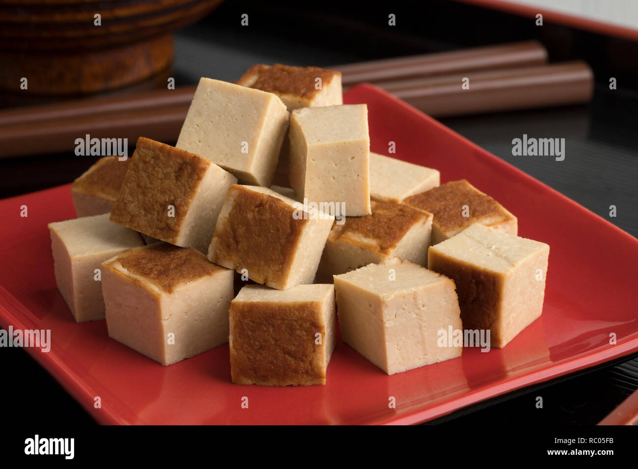 Cubes of smoked tofu on a red dish close up - Stock Image