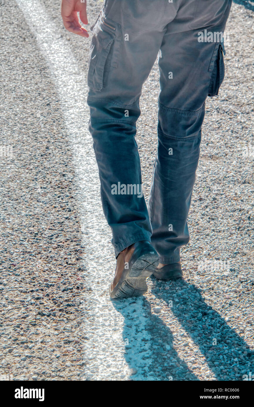 Unrecognizable person walking on the road - Stock Image