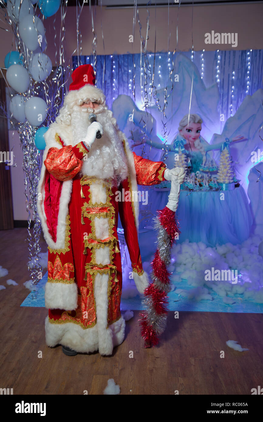 Father Frost speaks with a microphone . Santa Claus is singing Christmas songs against . Man in Santa Claus suit posing with microphone. - Stock Image