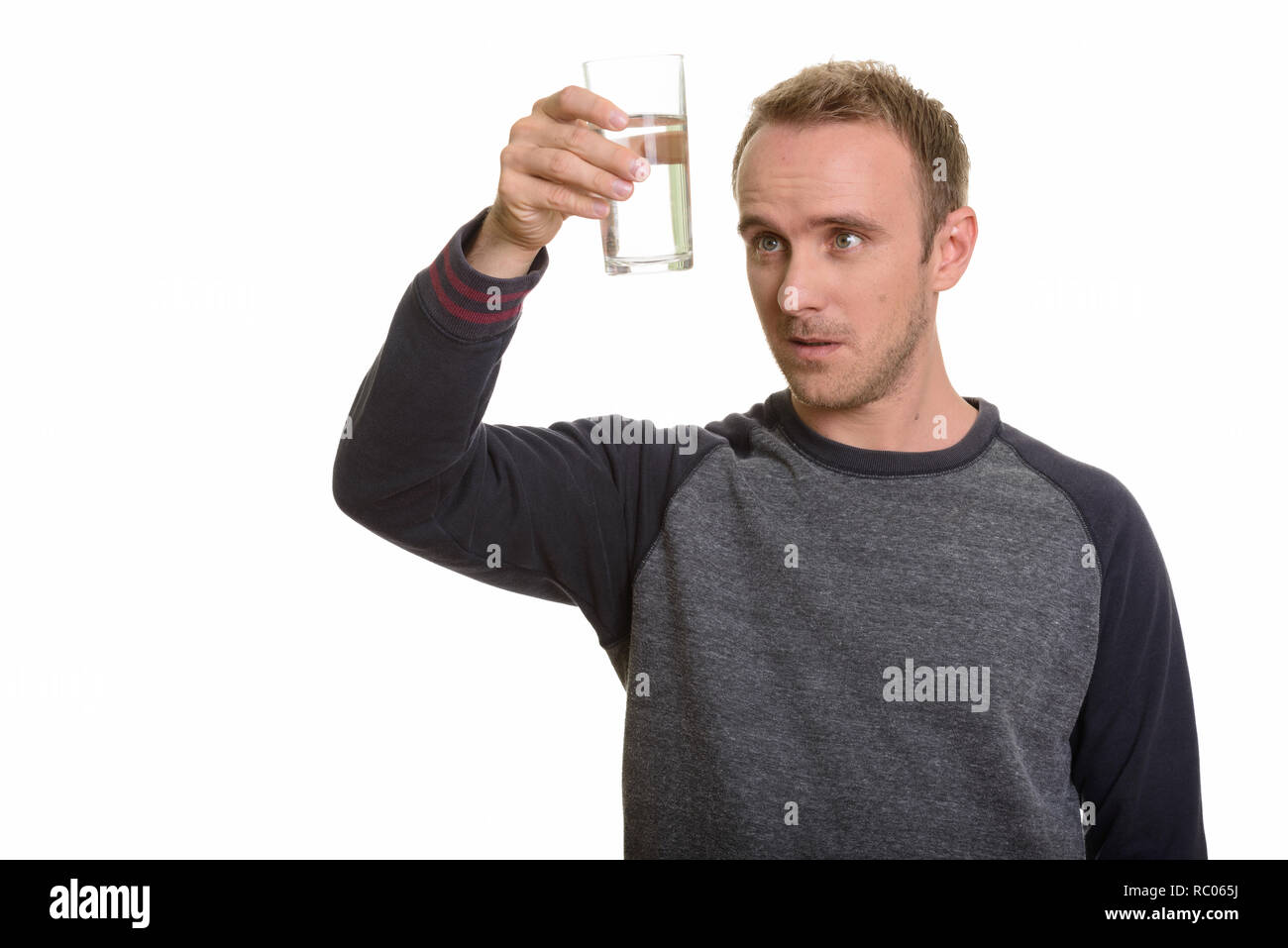 Handsome Caucasian man observing glass of water - Stock Image