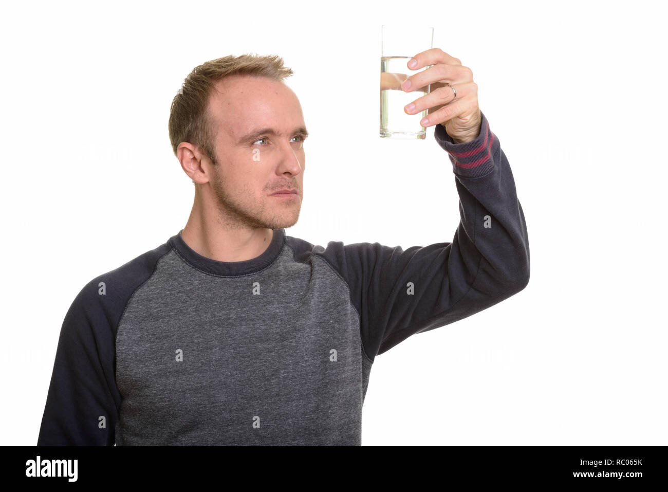 Handsome Caucasian man observing glass of water while thinking - Stock Image