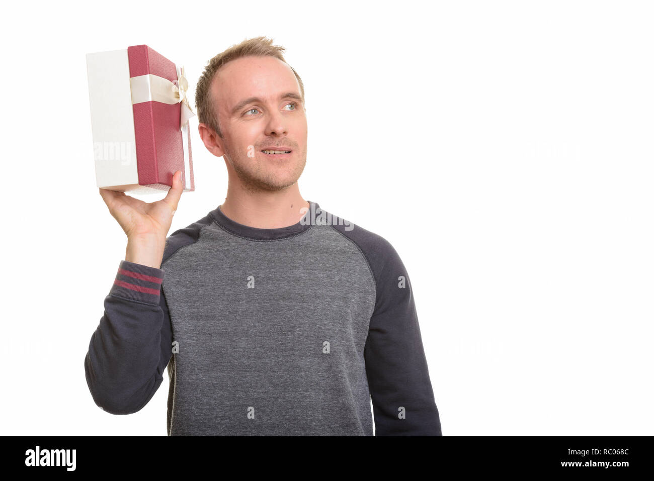 Happy handsome Caucasian man guessing gift while thinking ready  - Stock Image