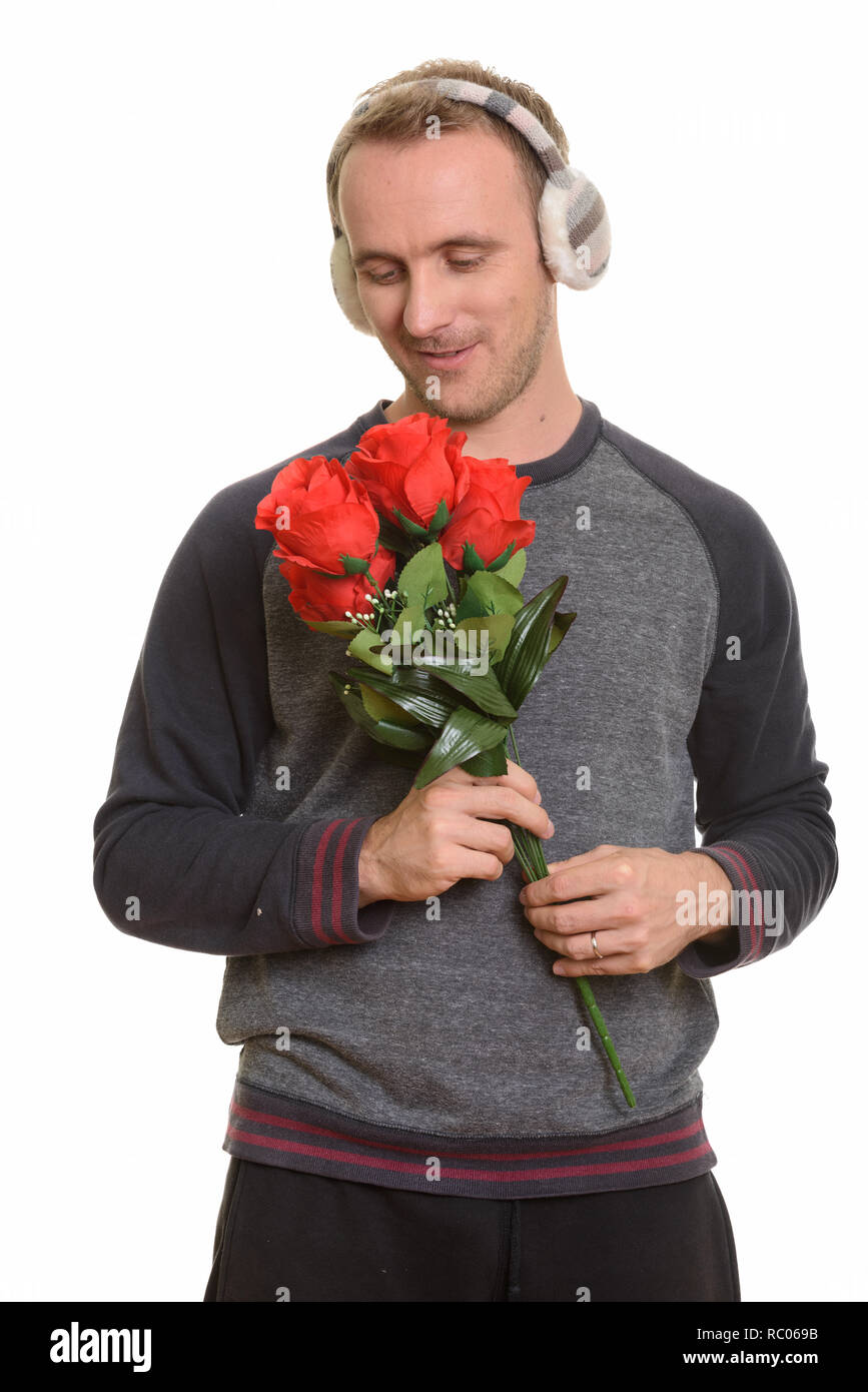 Handsome Caucasian man holding red roses ready for Valentine's d Stock Photo