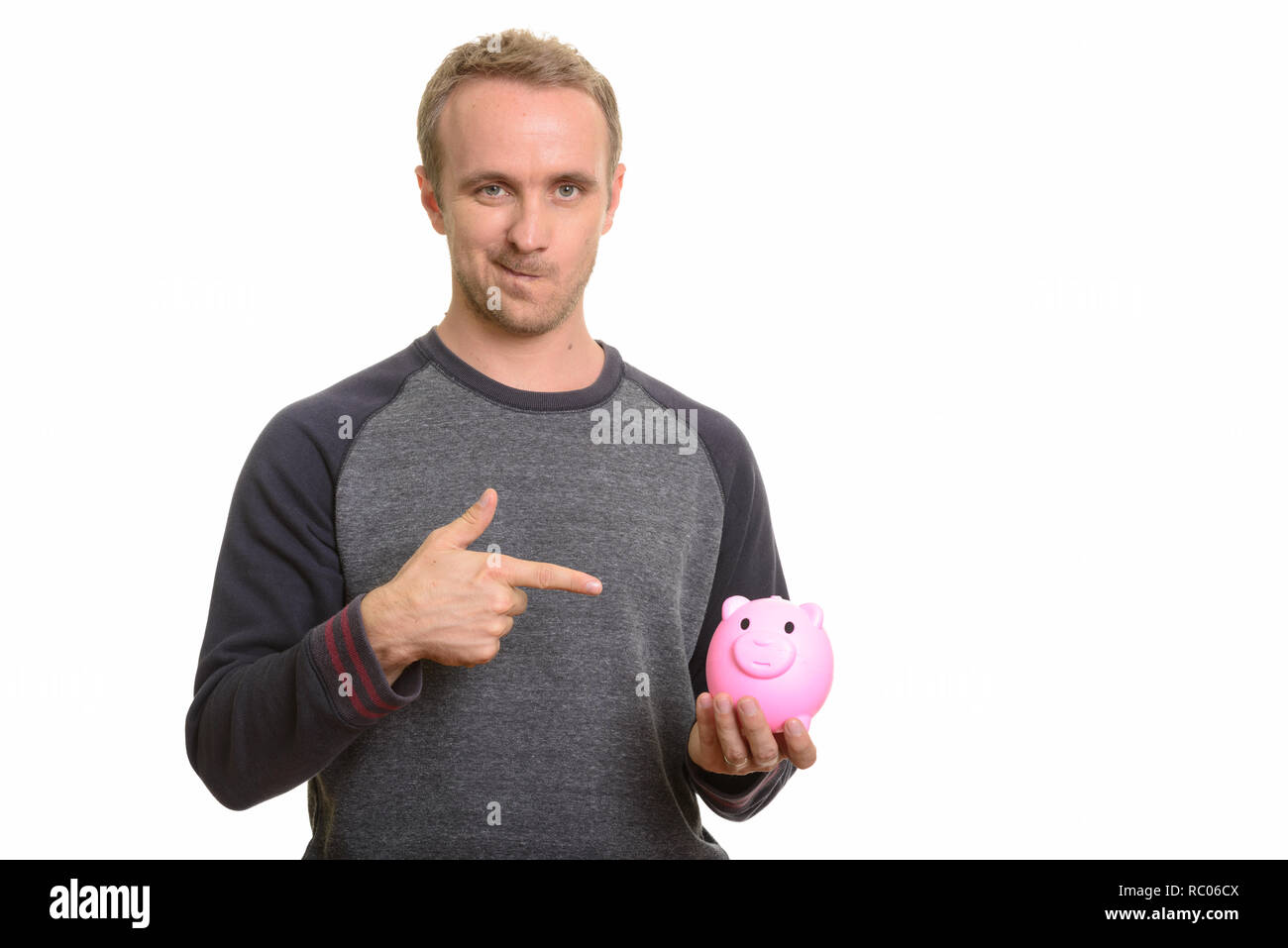Handsome Caucasian man holding piggy bank and pointing finger lo - Stock Image