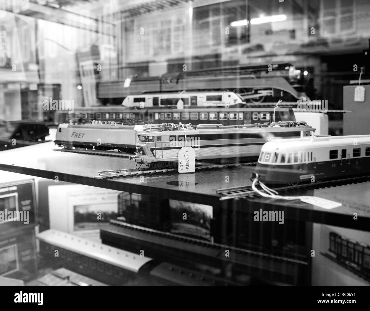 PARIS, FRANCE - JAN 30, 2018: Store window facade selling multiple toy collectible model trains featuring all railways in the world in central Paris, France black and white  - Stock Image