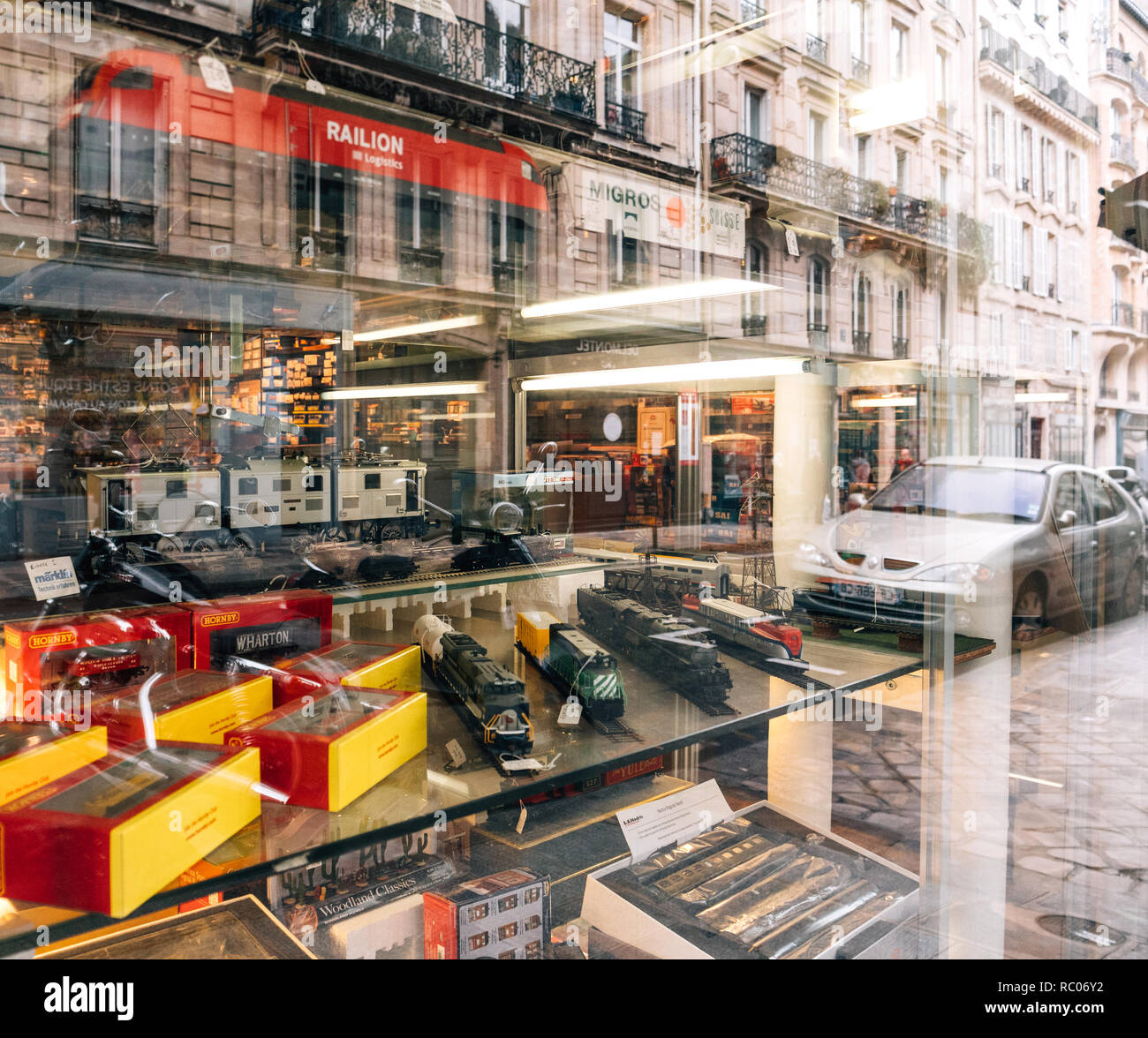 PARIS, FRANCE - JAN 30, 2018: Reflection Store window facade selling multiple toy collectible model trains featuring all railways in the world in central Paris, France Stock Photo