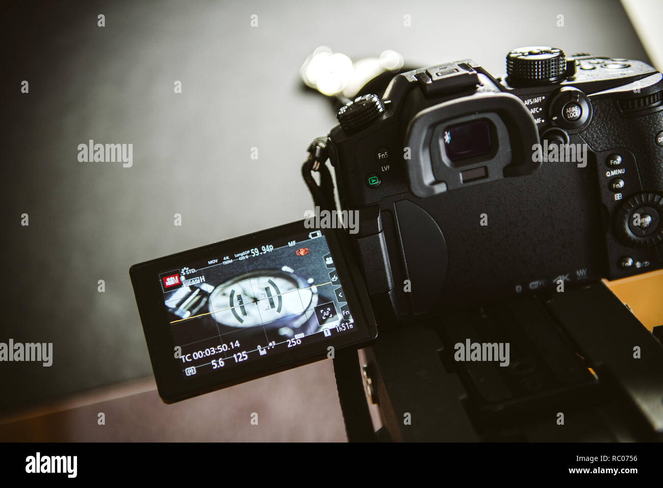 PARIS, FRANCE - APR 28, 2017: Vlogger making footage episode advertising with luxury swiss watch on photo table with Panasonic Lumix GH5 kit with Leica lens  - Stock Image