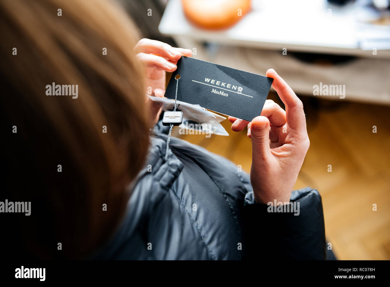 PARIS, FRANCE - FEB 2, 2018: Overhead view of woman wearing Max Mara Weekend Italian buy new fashionable down jacket reading price tag and logo Stock Photo