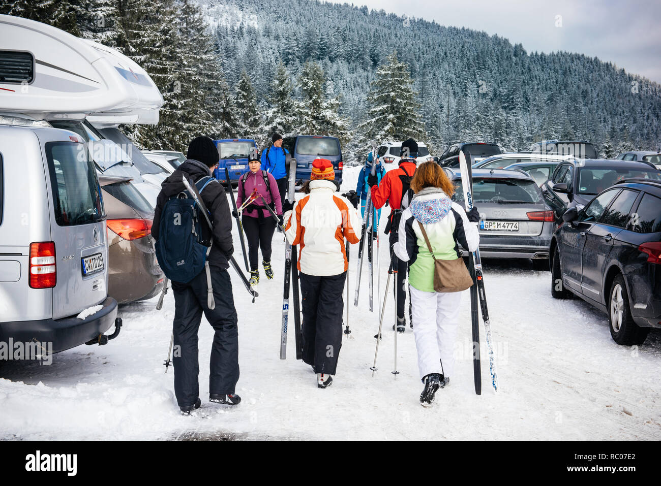 MUMMELSEE, GERMANY - FEB 18, 2018: Winter day with snow with rear view of group of friends in skiing equipment walking toward the slope or cars in the parking  - Stock Image