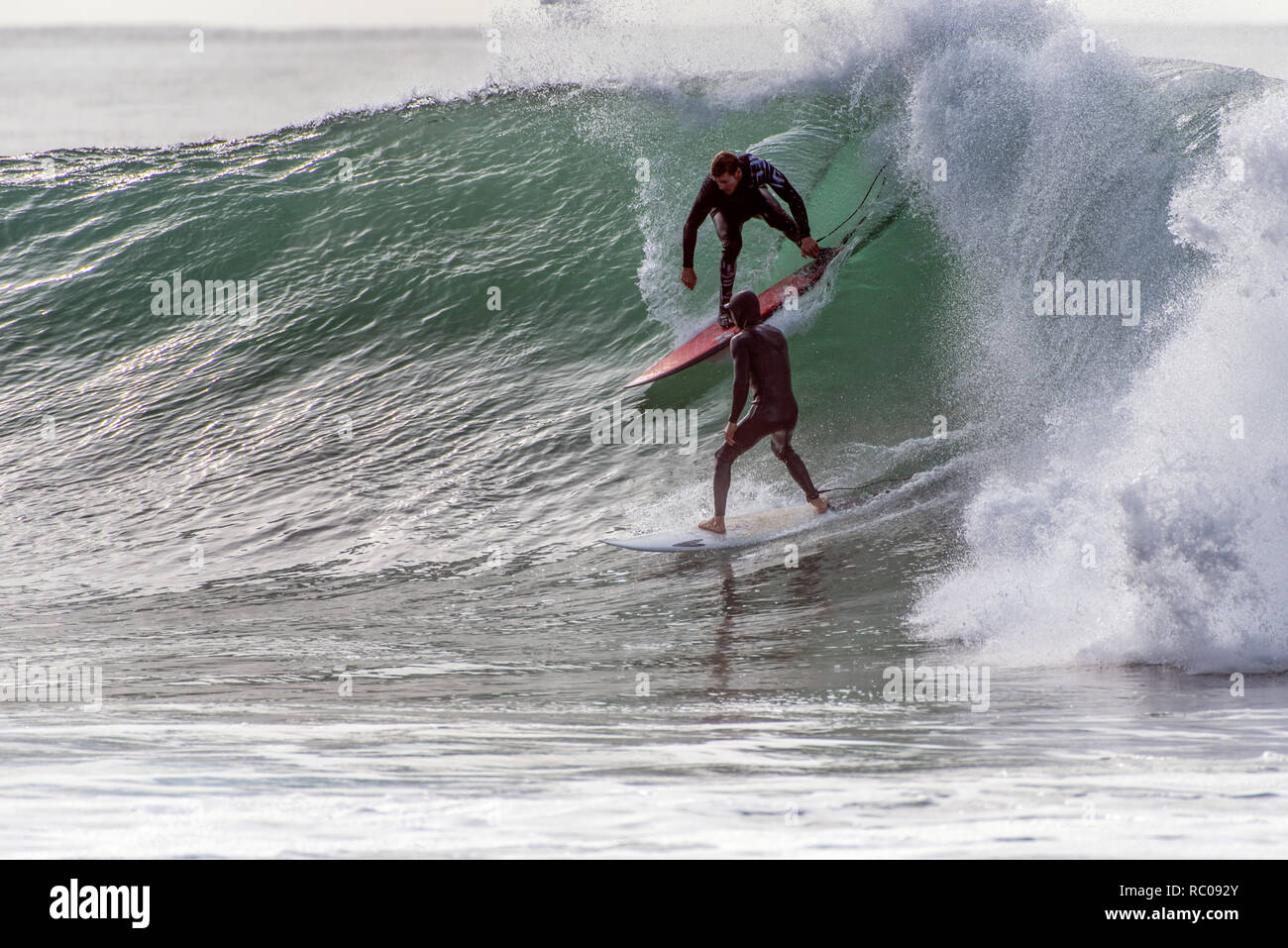 Crowded wave as one dropping in on another surfer's wave going right during winter swell in Santa Barbara, California, USA on January 9, 2019. - Stock Image