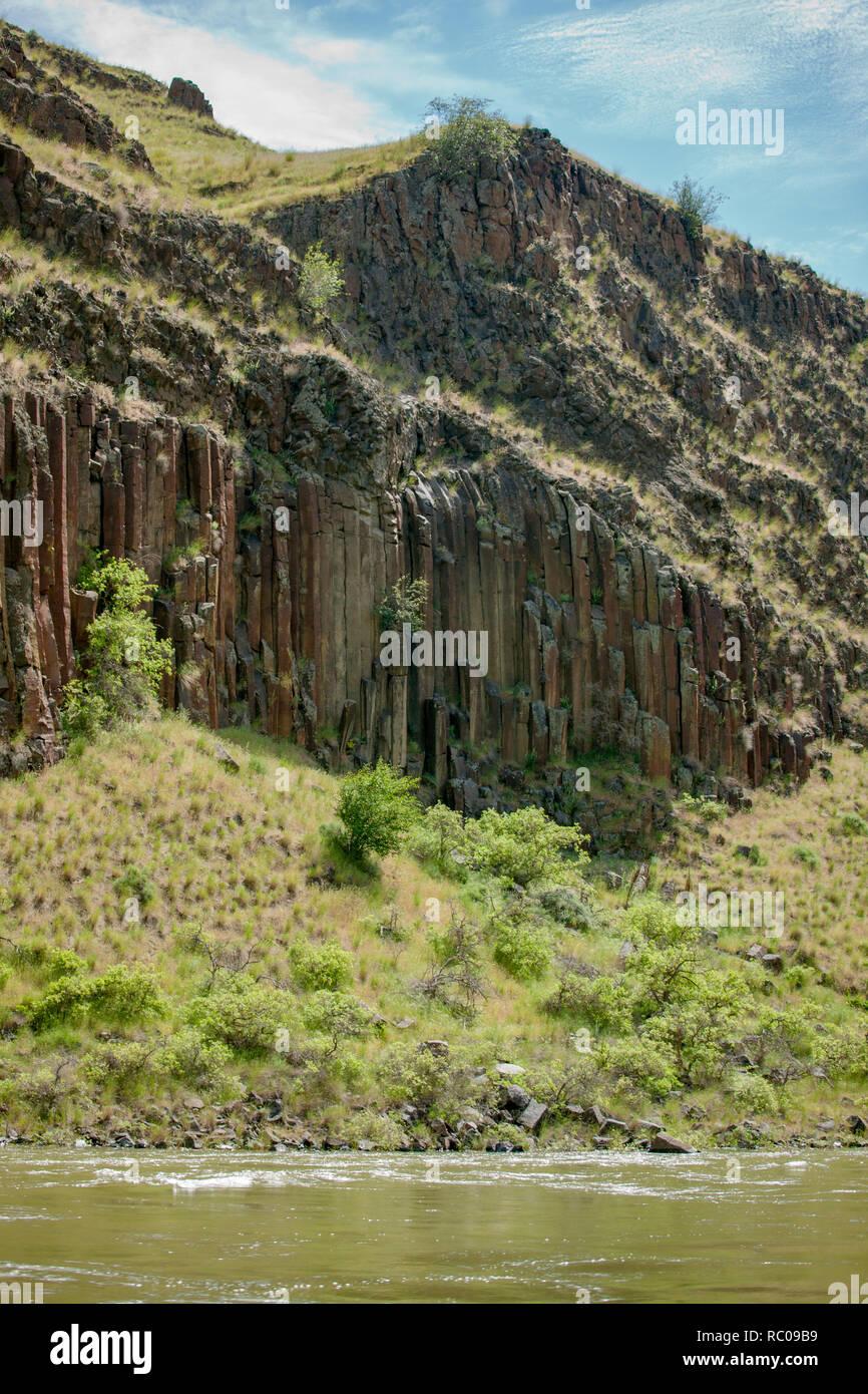 Rhyolite is an igneous rock.  The structures are referred to as columnar jointing.  Viewed fromSnake River in Hells Canyon National Recreation Area. - Stock Image