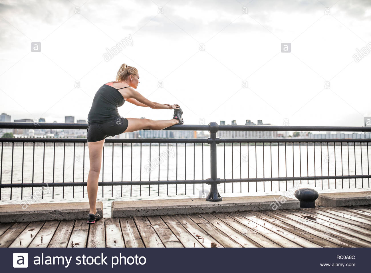 Young woman working out woman along shore, Montreal, Quebec, Canada Stock Photo