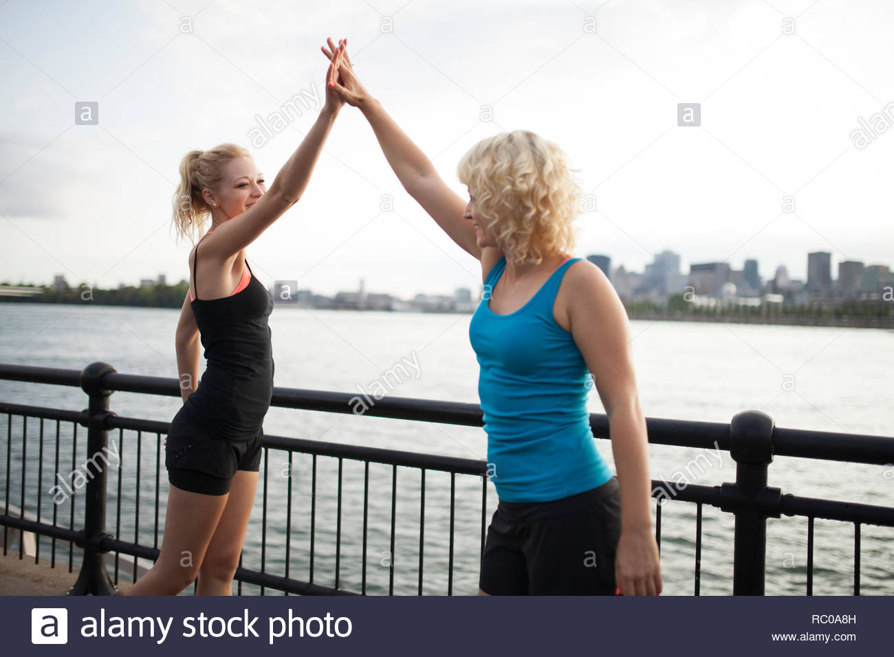 Two sisters clapping during workout together, Montreal, Quebec, Canada Stock Photo