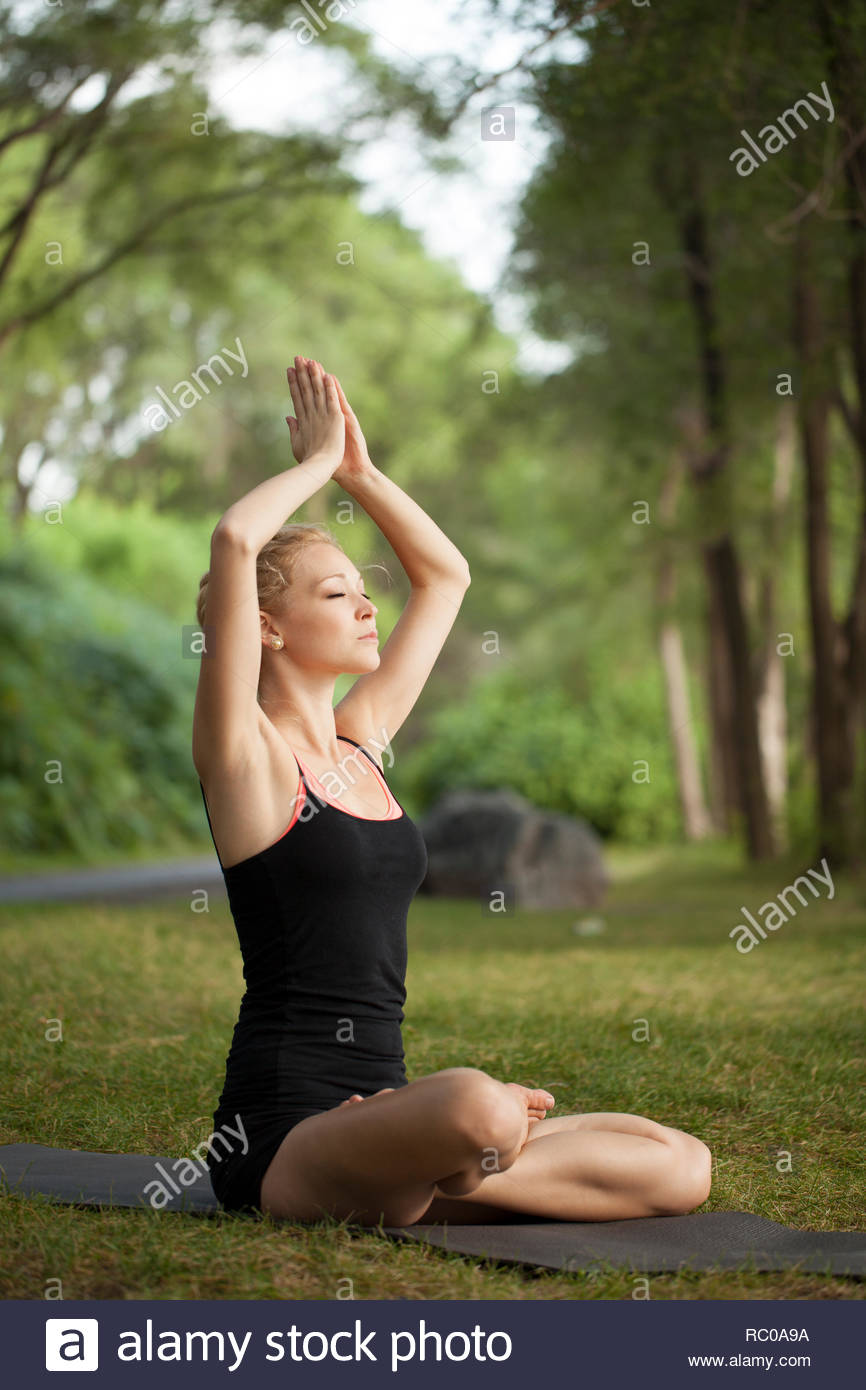 Young woman doing yoga working out in park Stock Photo