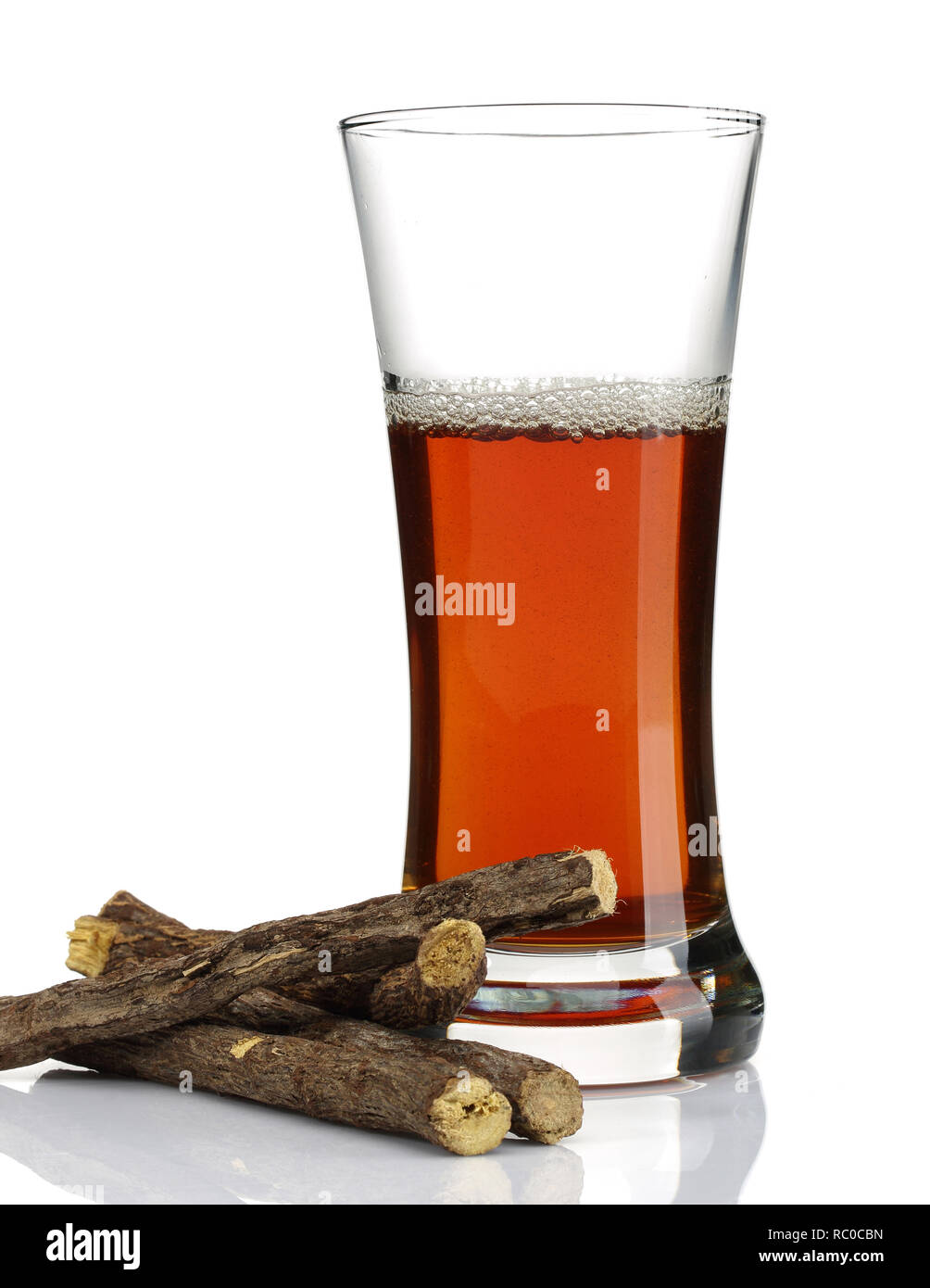 Liquorice root and a glass of tea isolated on white background - Stock Image