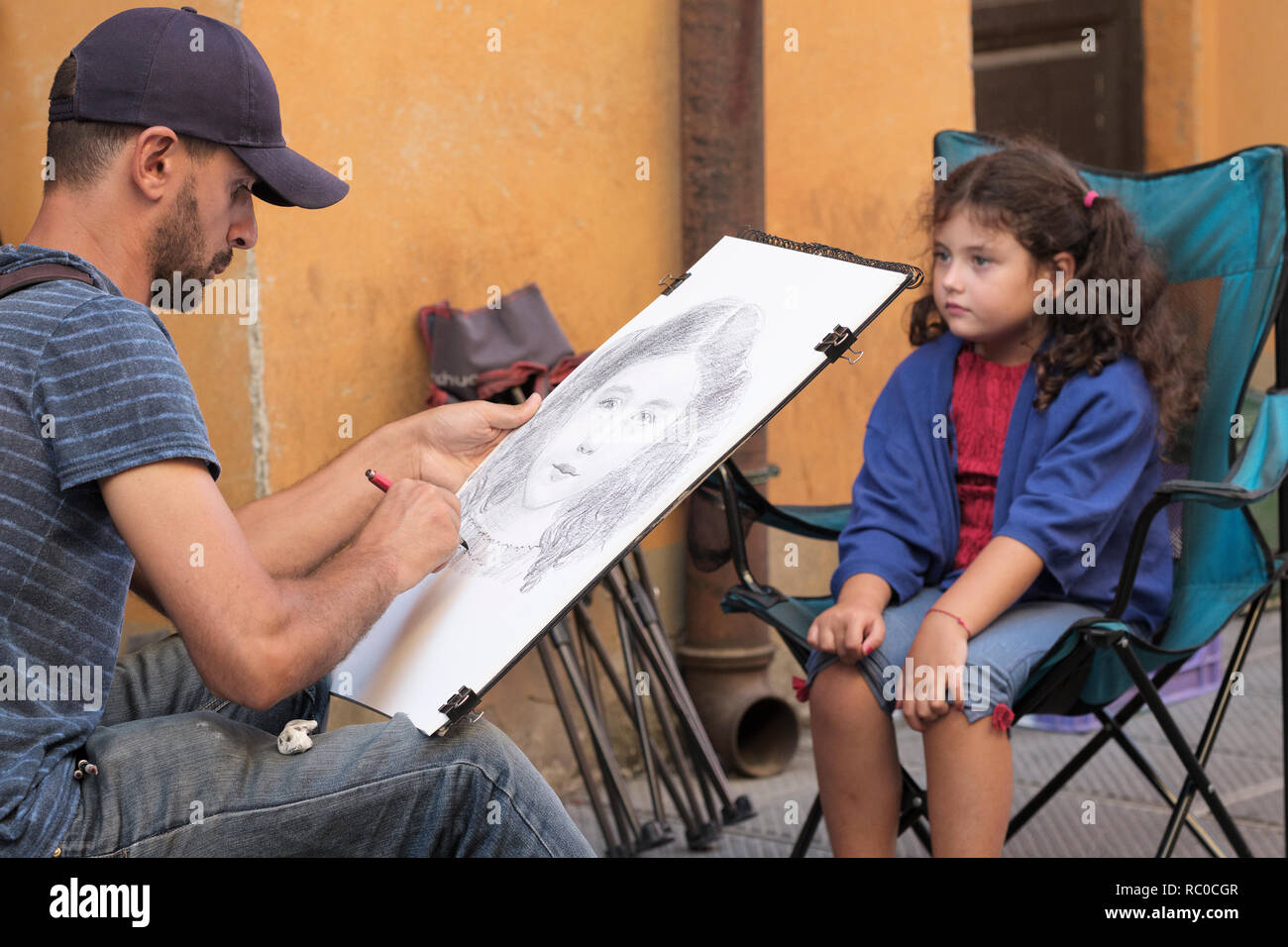 Street artist sketching young child in busy public street, Pisa,Tuscany, Italy, Europe, - Stock Image