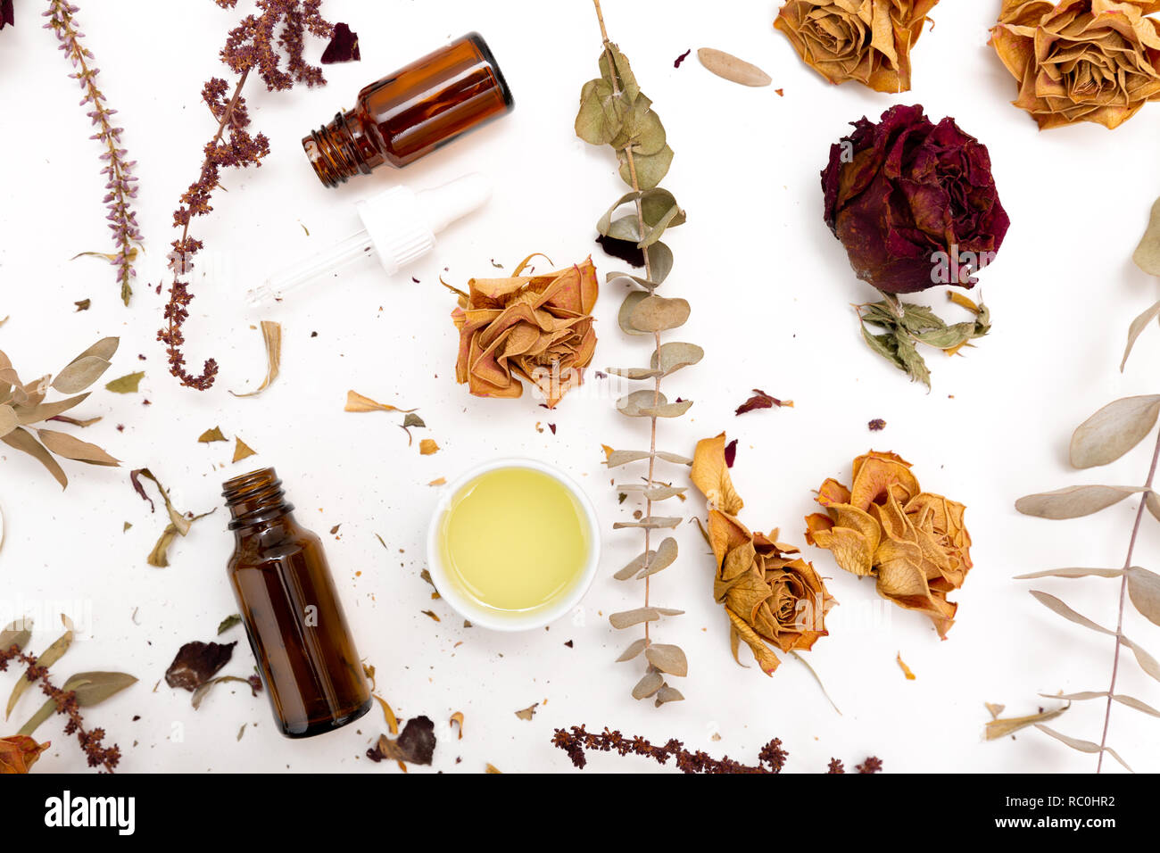 Aromatic botanical cosmetics. Dried herbs flowers mixture, facial mud clay mask, oils, applying brush. Holistic herbal skincare beauty hack Stock Photo
