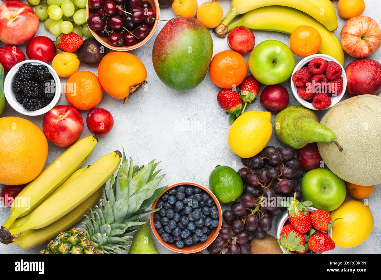 Healthy fruit background frame, strawberries raspberries oranges plums apples kiwis grapes blueberries mango persimmon on the white table - Stock Image