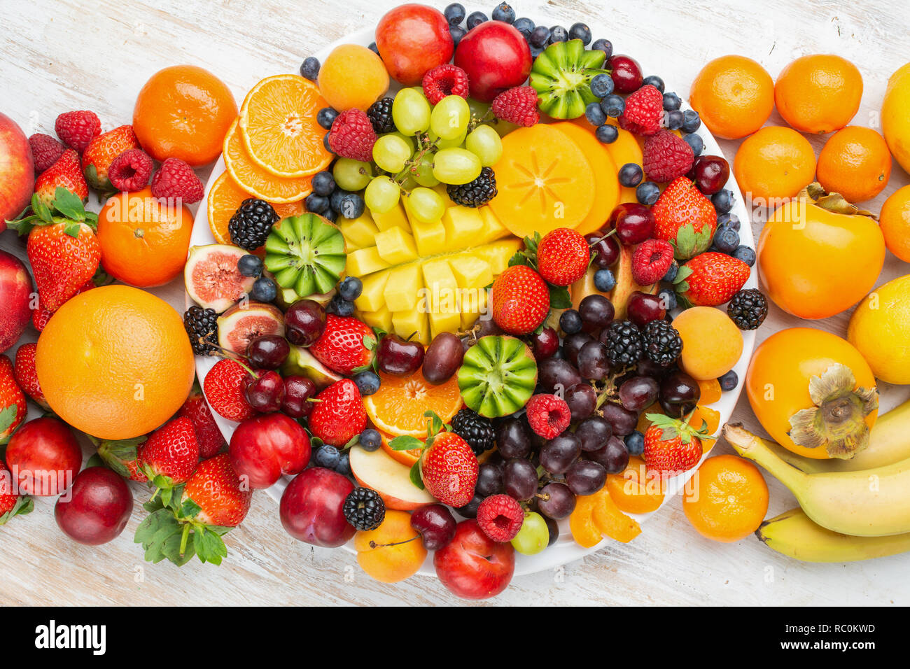 Healthy Platter With Colorful Rainbow Fruits Strawberries Raspberries Oranges Plums Apples Kiwis Grapes Blueberries Mango Persimmon Top View Stock Photo Alamy