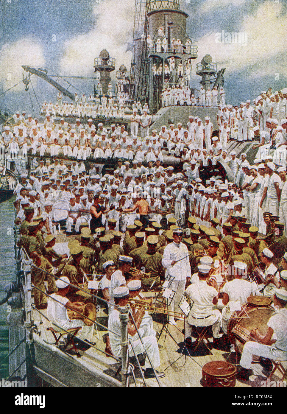 "The caption reads: ""Pack up your troubles in your old sea bag. All work and no play was not permitted to make the American sailor a dull boy."" The image dates to 1922 and shows American military on a carrier at sea in World War I. In the foreground a band with a conductor. In the middle is a boxing matched watched by a number of sailors. The others are more sailors and crew watching the events. Stock Photo"