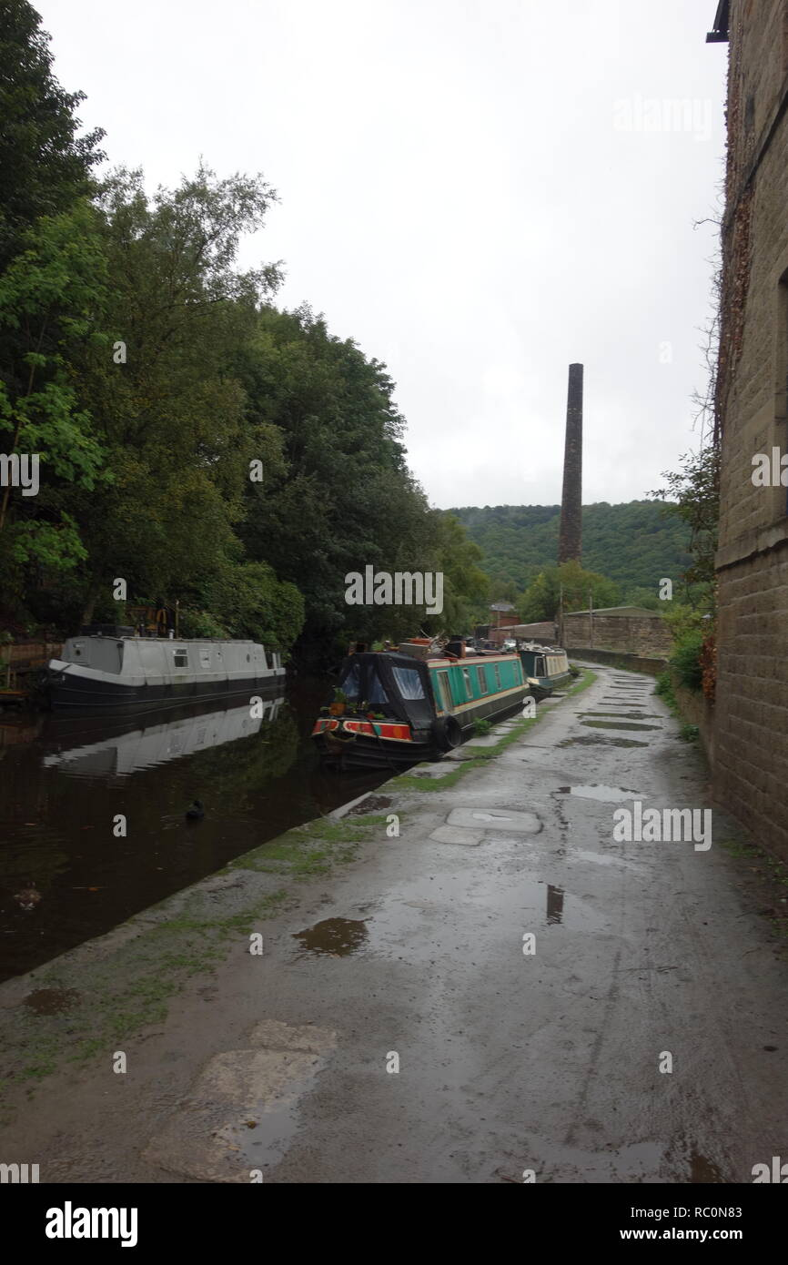Towpath beside the Rochdale Canal at Hebden Bridge with Sandstone chimney in background. - Stock Image