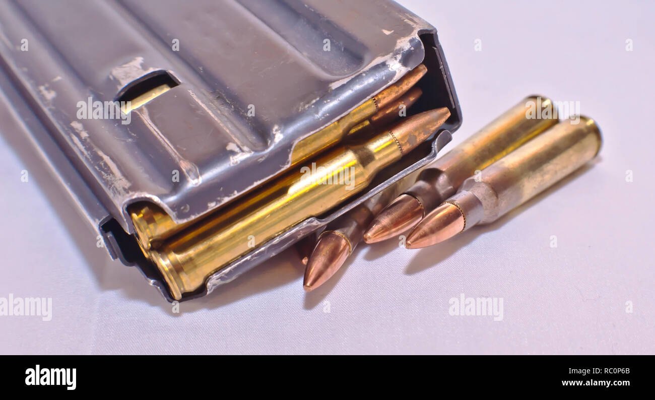 A loaded AR-15 rifle magazine on top of four .223 caliber bullets on a white background - Stock Image