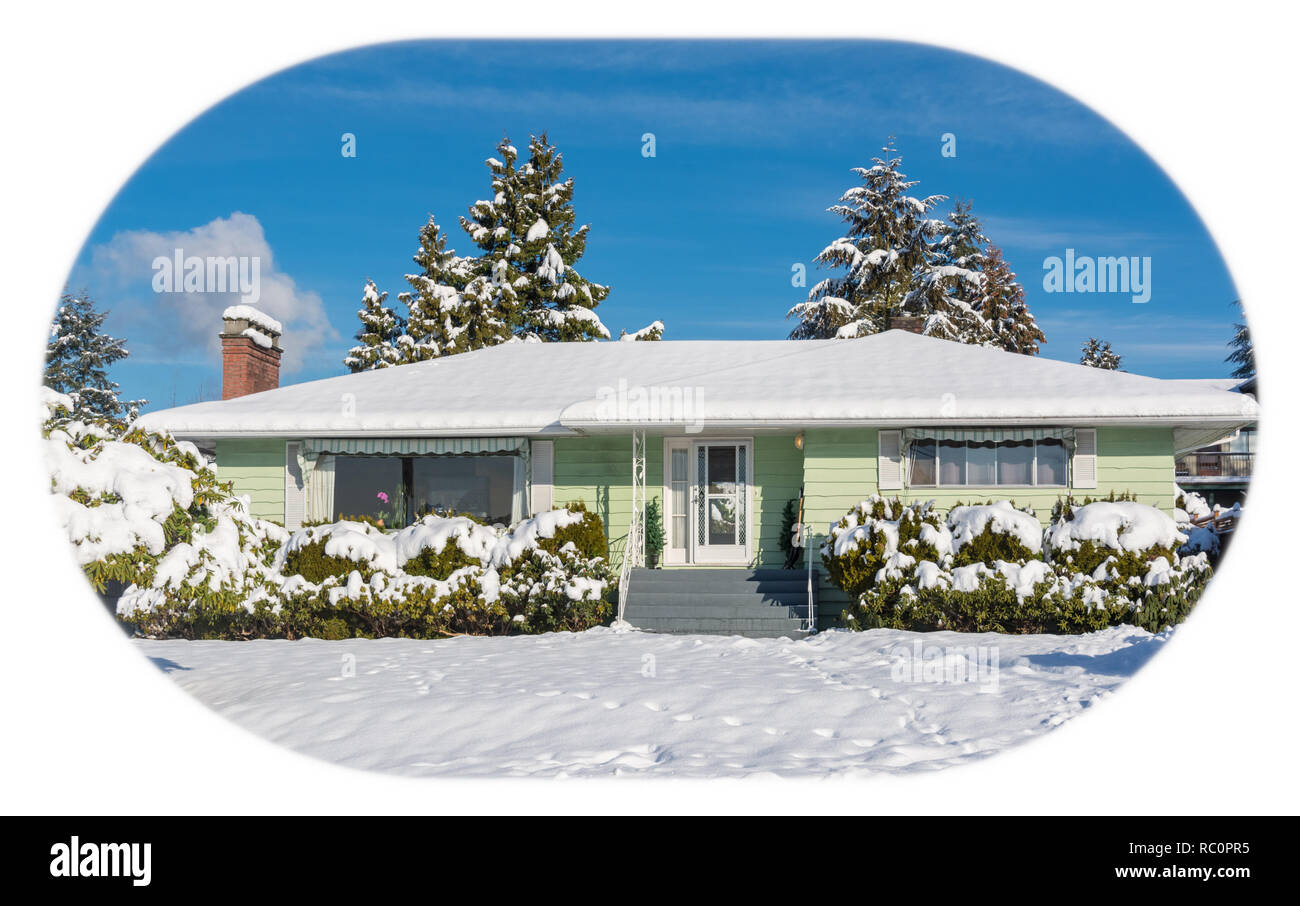 Family residential house with front yard in snow. North American house on winter sunny day - Stock Image