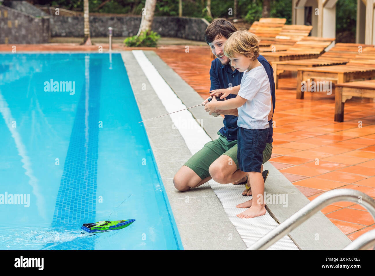 Father and son playing with a remote controlled boat in the pool. - Stock Image