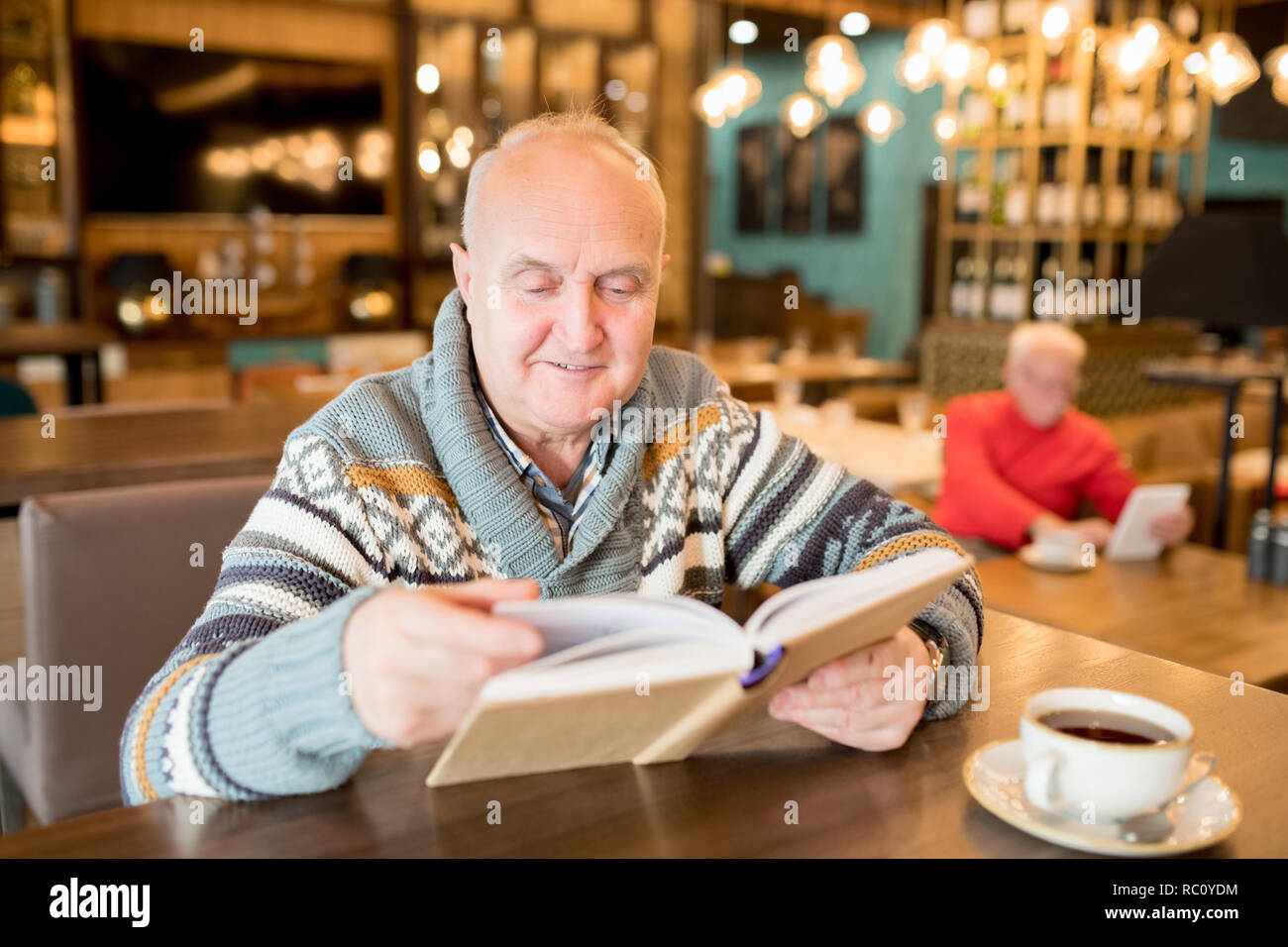 Curious chubby man reading interesting book in cafe - Stock Image