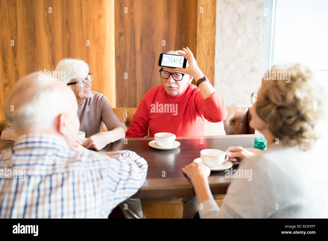 Seniors playing word-guessing game in cafe - Stock Image