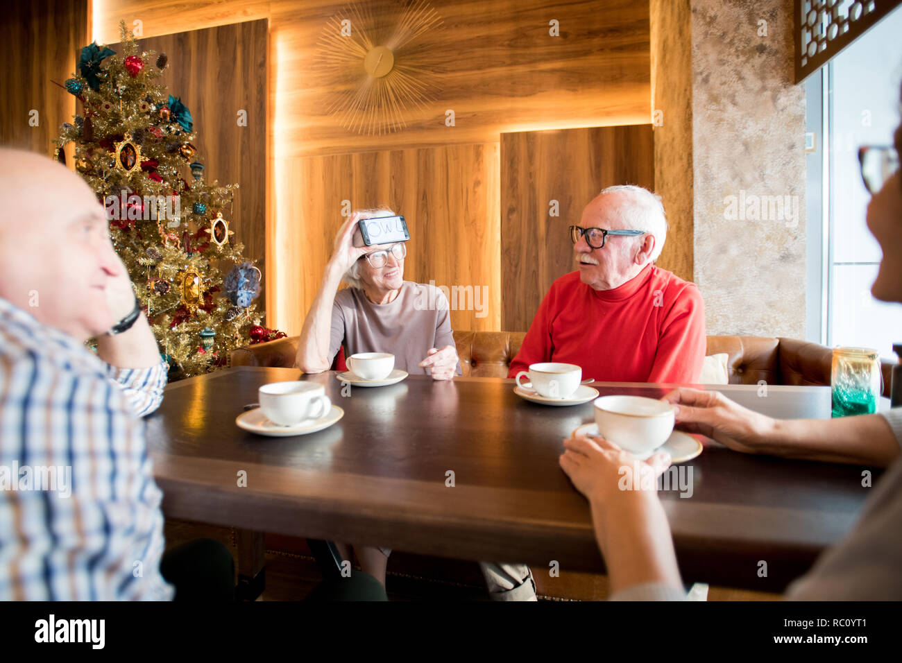 Positive senior lady asking questions to friends while guessing  - Stock Image