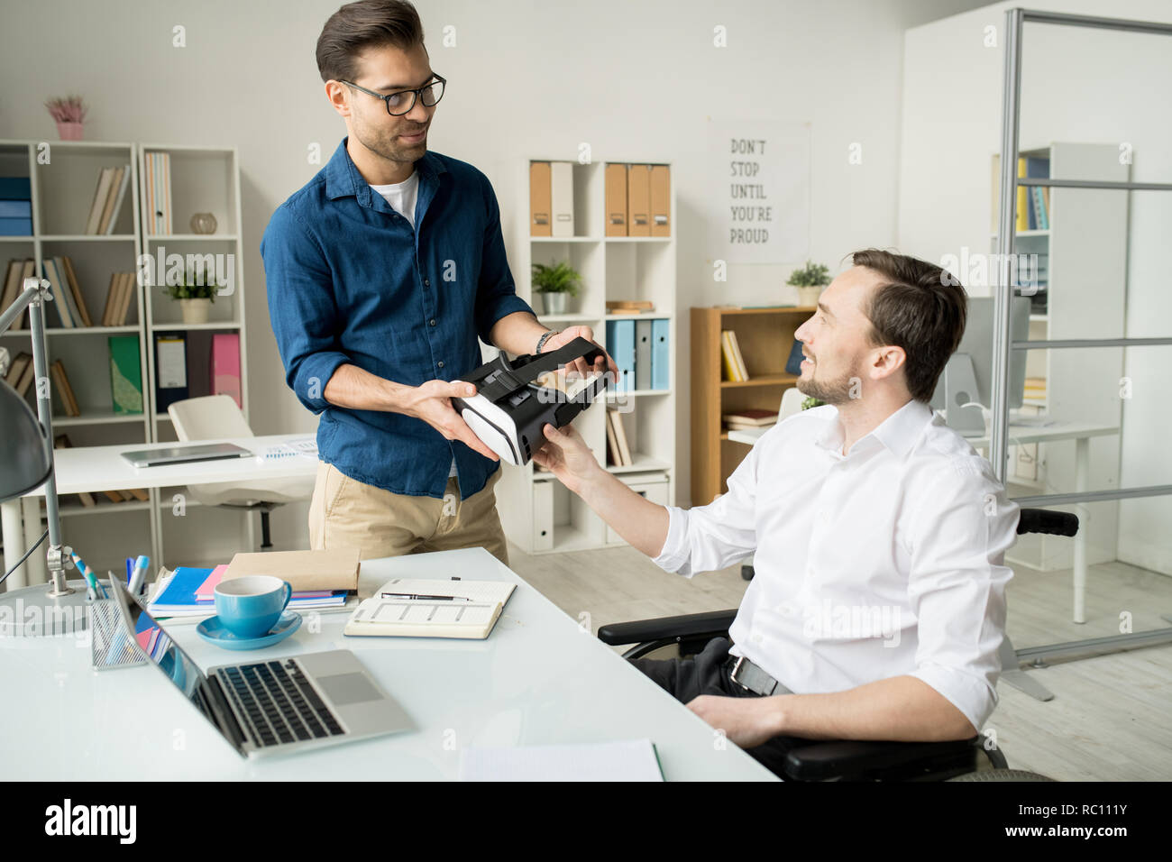 Business colleagues discussing new gadget - Stock Image