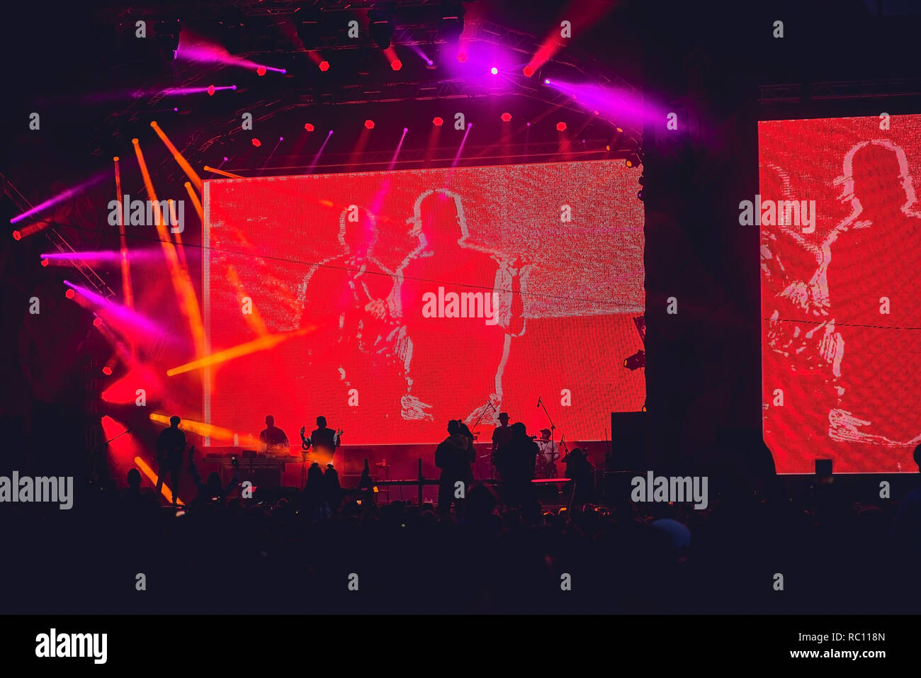 Silhouette of a big crowd at concert against a brightly lit stage. Night time rock concert with people having fun lifting hands up in the air and chee - Stock Image