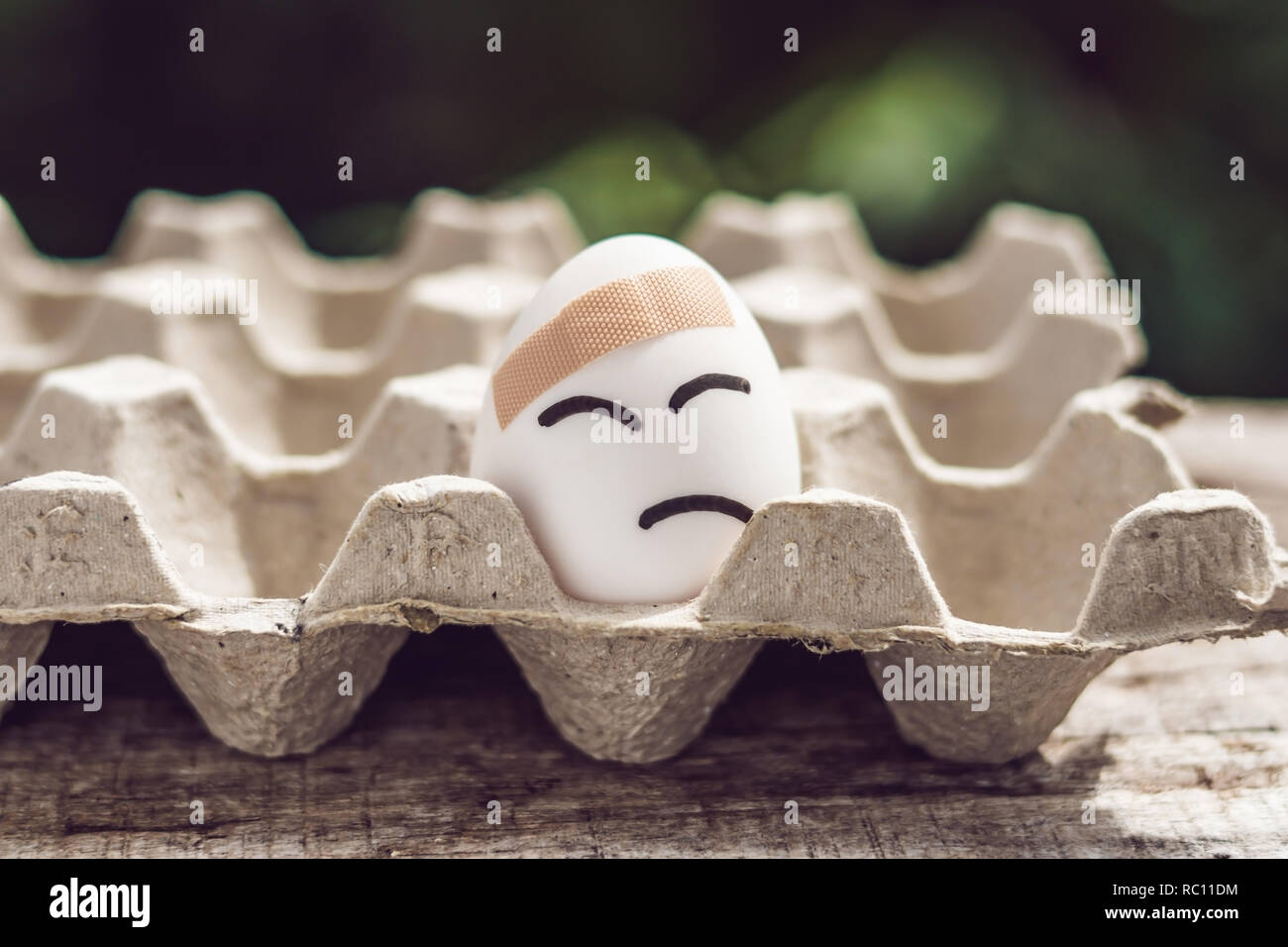 Broken egg with sticking plaster. Concept of brittleness and pain. - Stock Image