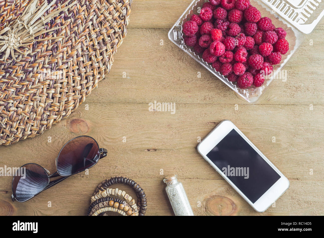 Summer holiday, vacation, relaxation concept. Raspberries, straw hat, smartphone, sunglasses from above, top view, flat lay on wooden background. Free text copy space. Summer vibes concept. Stock Photo