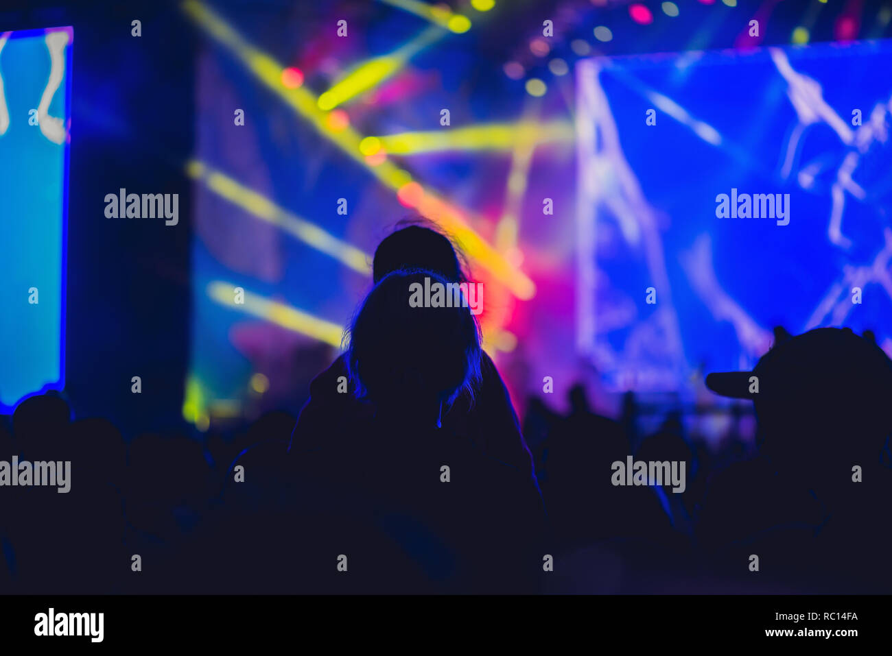 Silhouette of a big crowd at concert against a brightly lit stage. Night time rock concert with people having fun lifting hands up in the air and cheering the musicians - Stock Image