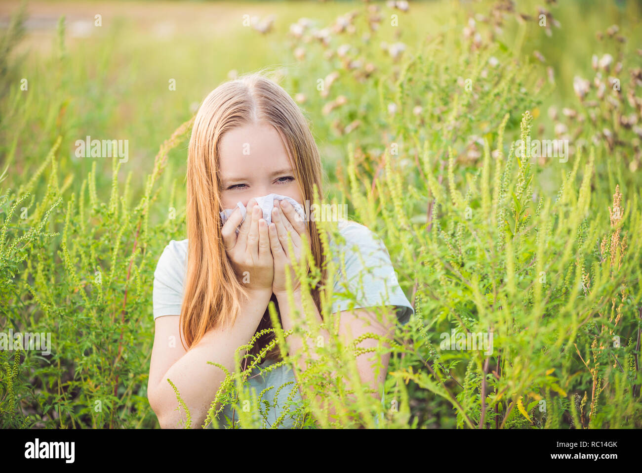 Young woman sneezes because of an allergy to ragweed Stock Photo