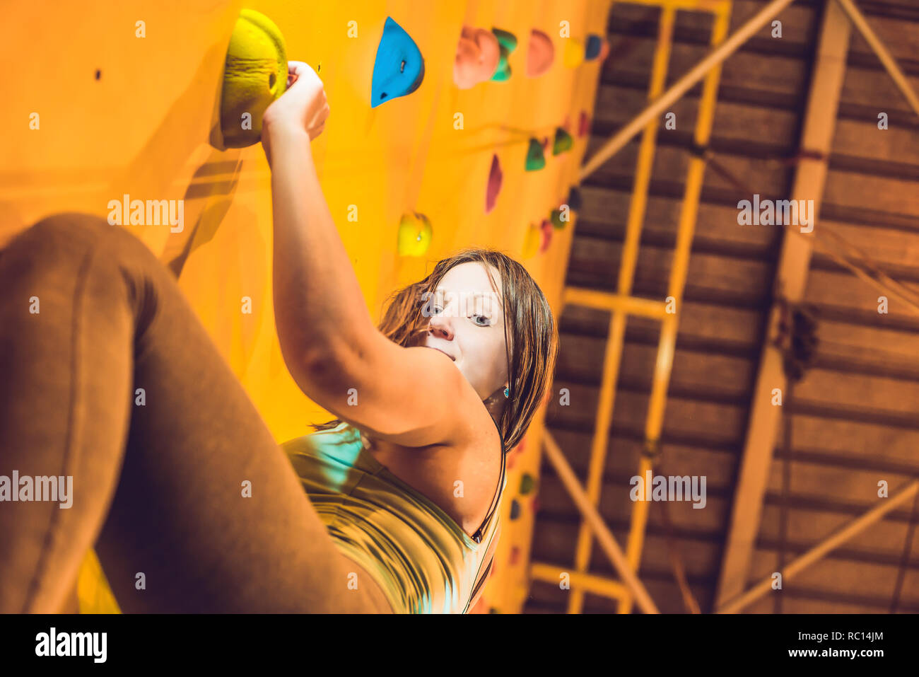attractive young professional sport climber woman having training in the gym at artificial wall - Stock Image